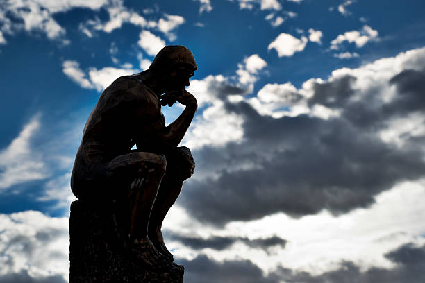 Replica of Rodin's The Thinker with sky background stock photo