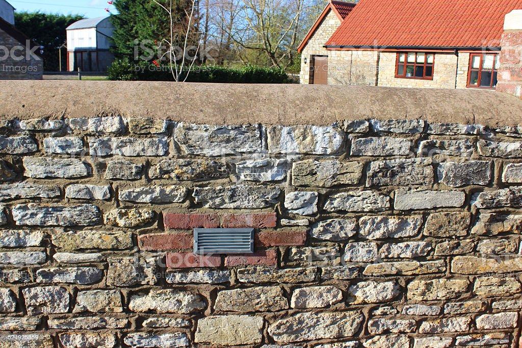 Repointed acciottolato muro di pietra con illuminazione da