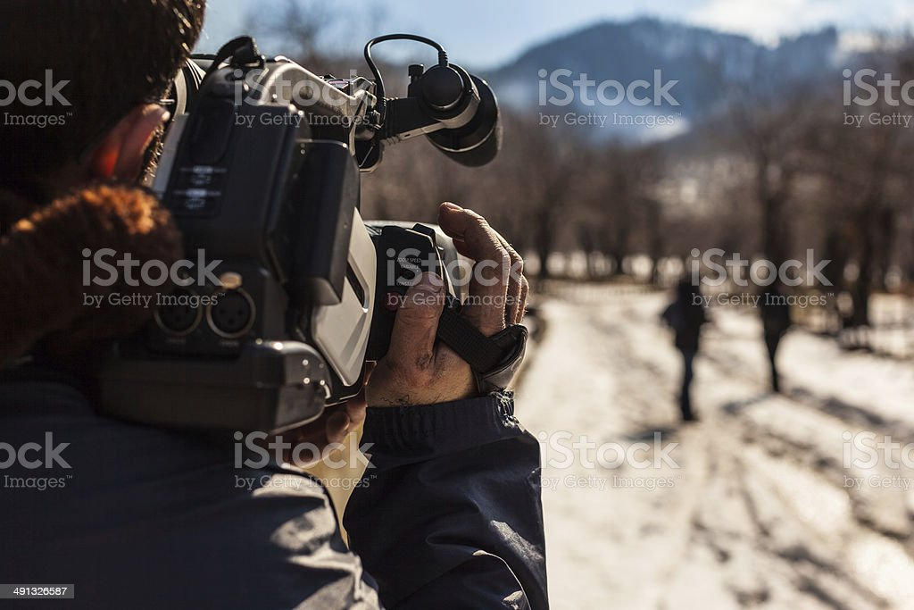 report a young man using a professional camcorder outdoor Adult Stock Photo