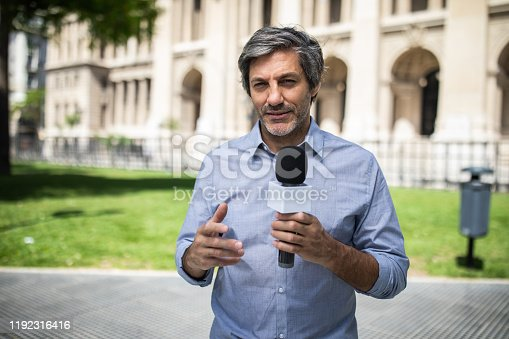 Mature journalist with gray hair talking in microphone in park on sunny day in Buenos Aires