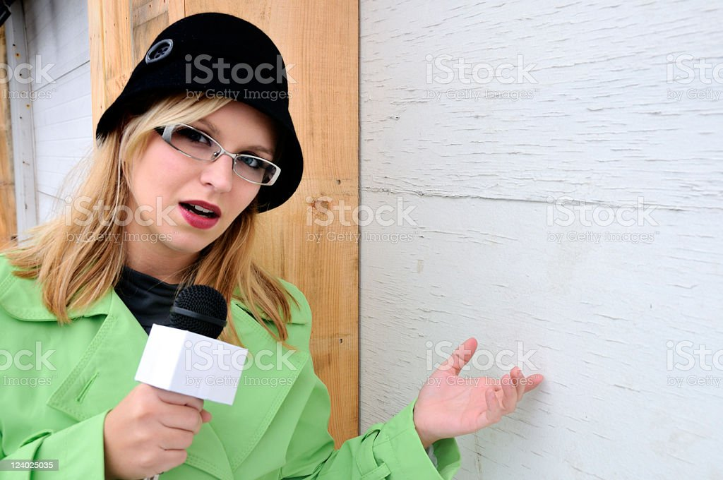 Reporter Gestures to Boarded Up Business (Copyspace) stock photo