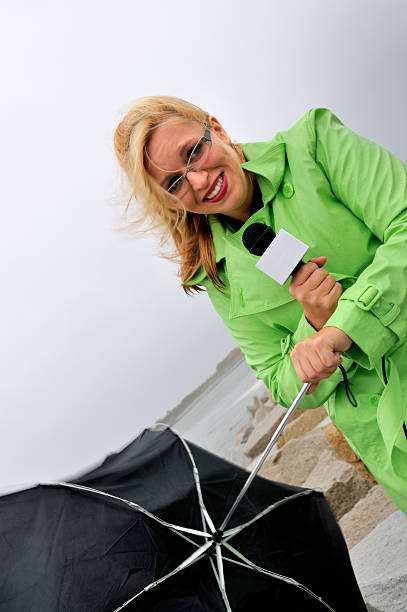 Reporter Shrugs Off Weather with a Smile stock photo