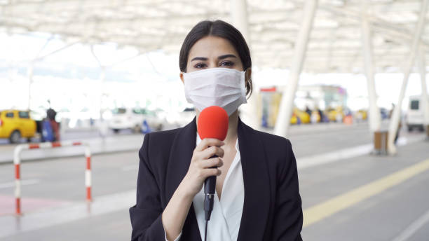 TV reporter wearing a mask stock photo