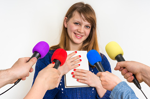 Reporters with microphones making interview with book writer - journalism and broadcasting concept