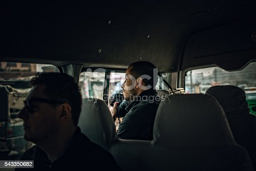 Photo of a news reporters sitting in a van, waiting for a story to capture
