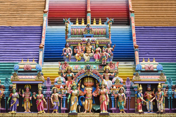 (Selective focus) Representation of Hindu gods and tourists climbing a colorful stairs leading to the Batu Caves in the background. Kuala Lumpur, Malaysia (Selective focus) Representation of Hindu gods in the foreground and a colorful stairs leading to the Batu Caves in the background. Batu Caves is a limestone hill with a series of caves and cave temples in Gombak, Selangor, Kuala Lumpur, Malaysia. kuala lumpur batu caves stock pictures, royalty-free photos & images