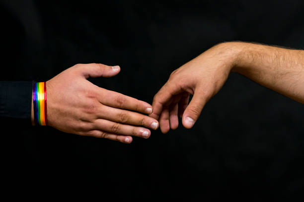 Representative of the LGBT community. Hands reach out for a handshake with a young man. stock photo