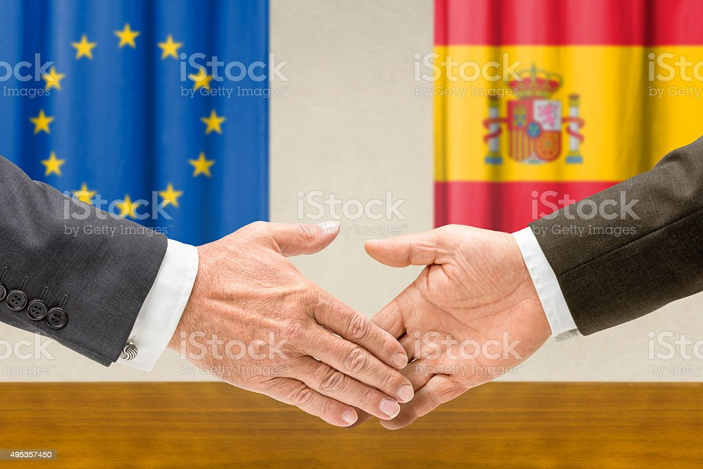 Representatives of the EU and Spain shake hands stock photo