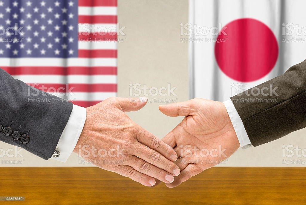 Representatives of the USA and Japan shake hands stock photo