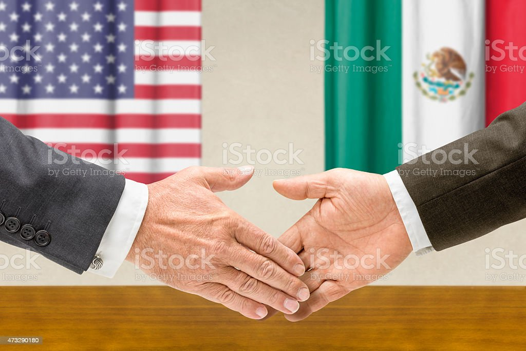 Representatives of the USA and Mexico shake hands stock photo
