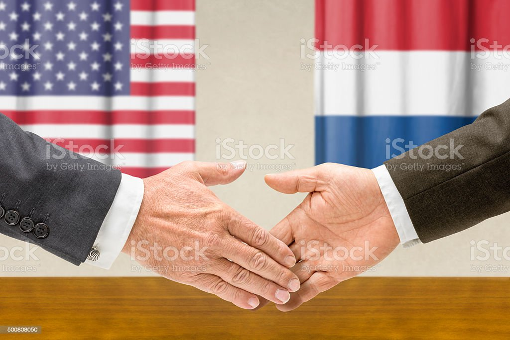 Representatives of the USA and the Netherlands shake hands stock photo