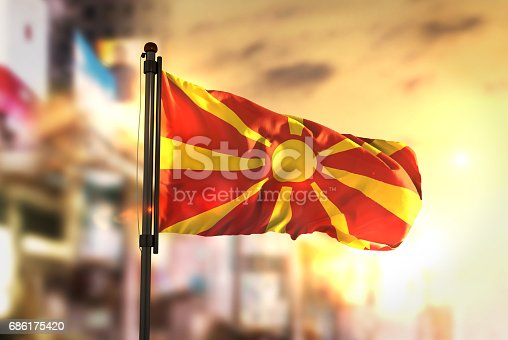 686175420 istock photo Republic of Macedonia Flag Against City Blurred Background At Sunrise Backlight 686175420