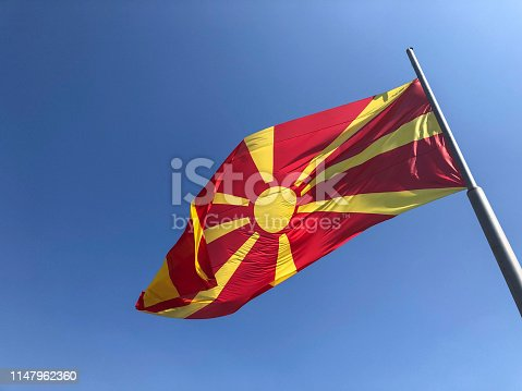 686175420 istock photo Republic of North Macedonia flag waving on sky 1147962360