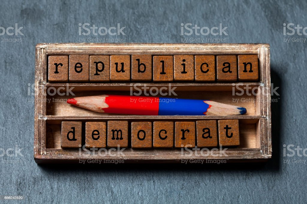 Republican democrat politic alternative choice concept. Vintage box, wooden cubes phrase with old style letters, red blue colored pencil. Gray stone textured background. Close-up, up view, soft focus stock photo