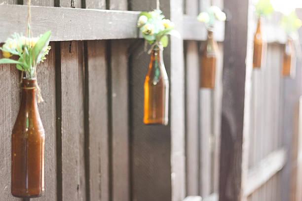 - purposed flaschen = outdoor-vasen - rustikaler hinterhof stock-fotos und bilder