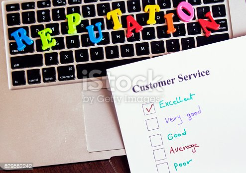 reputation word colorful letters above keyboard and chooses excellent on a customer service survey