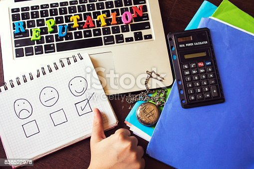 woman hand drinking  a coffee and reputation word colorful letters above keyboard and chooses happy face