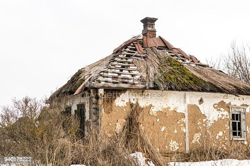 Old abandoned house. Weathered ruined building with broken straw roof. Aged rural home made of rocks,  stone and clay.