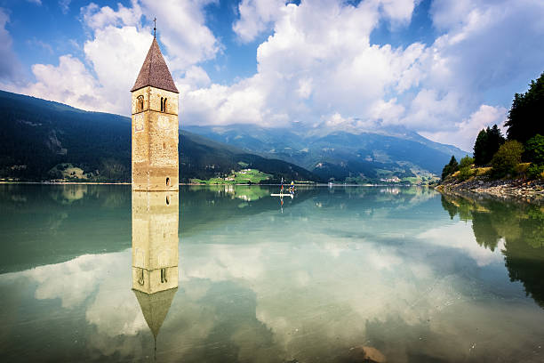 reschenpass famous historic bell tower at the reschenpass - italy bell tower tower stock pictures, royalty-free photos & images