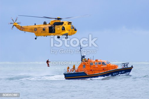 Eastbourne, United Kingdom - August 17, 2014: RAF Rescue helicopter and RNLI rescue boat demonstrating their skills during the Eastbourne AirShow.