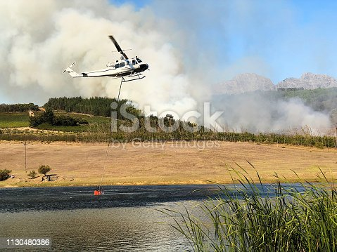 A rescue helicopter with a bucket of water hanging below on the way to a bush fire against a clear blue sky flying off to the pine woodlands behind near Stellenbosch South Africa