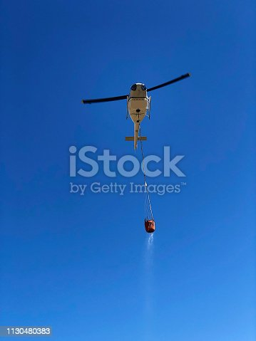 A directly below image of a rescue helicopter with a bucket of water hanging below dripping on the way to a bush fire against a clear blue sky near Stellenbosch South Africa