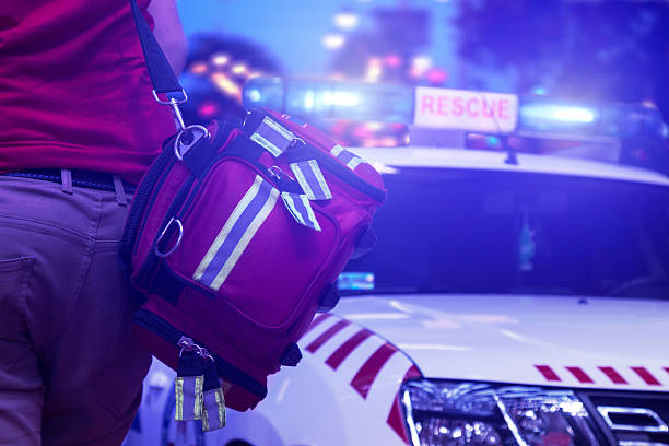 Rescue public service in action Back view of rescue service team member holding a bag and standing next to the vehicle with rotating beacons  accidents and disasters stock pictures, royalty-free photos & images