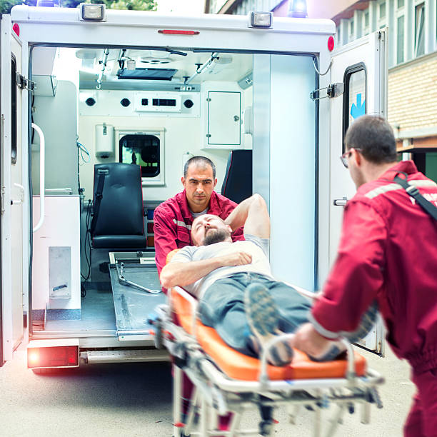 Rescue Team Providing First Aid Medical emergency team helping injured man ambulance staff stock pictures, royalty-free photos & images