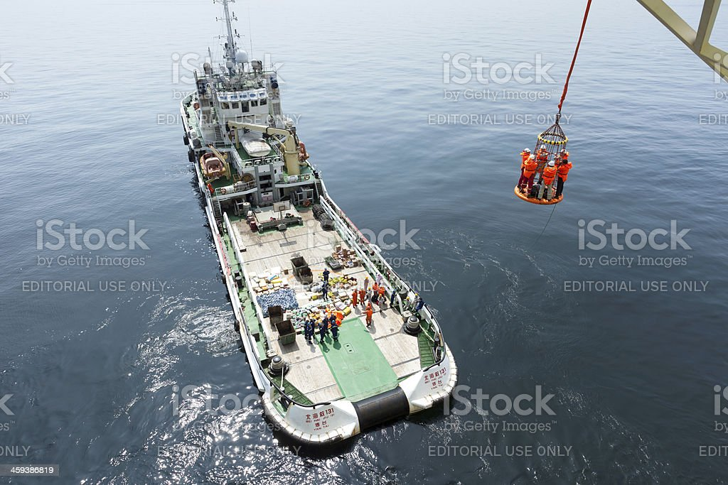 rescue tug boat resupply to oil drill platform royalty-free stock photo