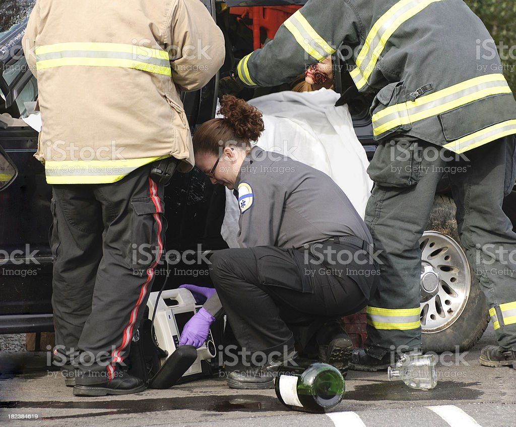 Two EMTs and a fireman work quickly to monitor and free a trapped...