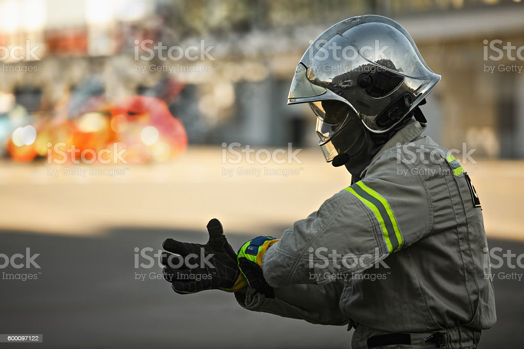 Rescuer and burning car stock photo