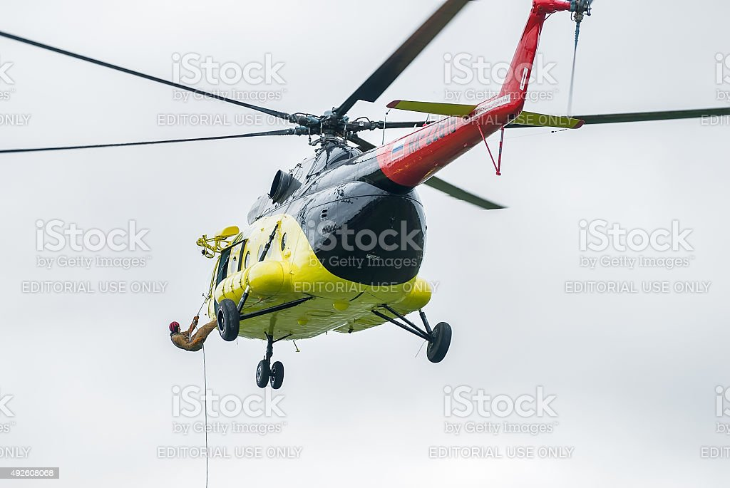 Rescuer is landed from MI-8 helicopter by rope stock photo
