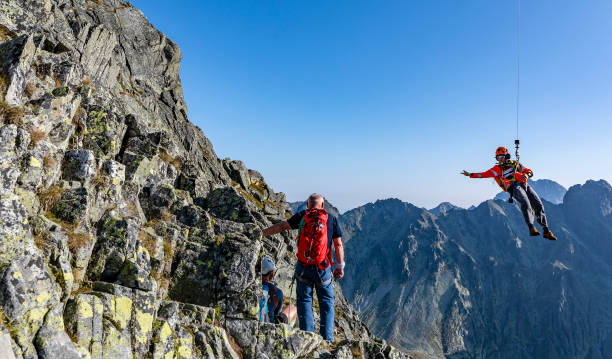 Retter (Horska, HZS) auf einem Seil von einem Hubschrauber auf einen Bergpass zu einem verletzten Touristen, der mit einem Führer auf Gerlach ging. – Foto