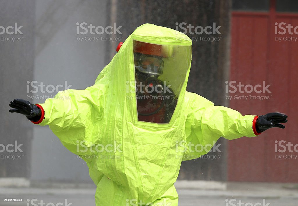 rescuer with the yellow suit against biological hazard from cont stock photo