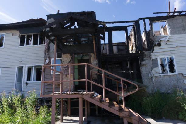 räddningsarbetare brandmän släcka en brand på taket. byggnaden efter branden. brända fönster. förstörda hus. katastrof. sot på fönstren. - brand sotiga fönster bildbanksfoton och bilder