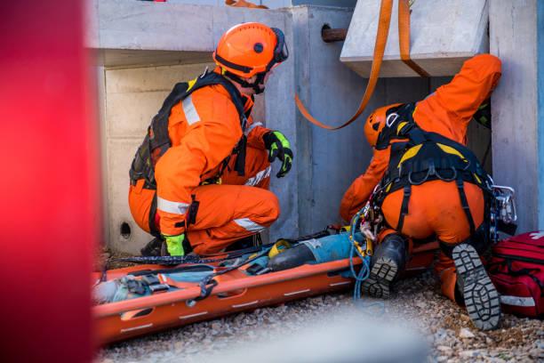 het redden van gewonde persoon uit de ruïnes, redden brandweerlieden operatie - red stockfoto's en -beelden