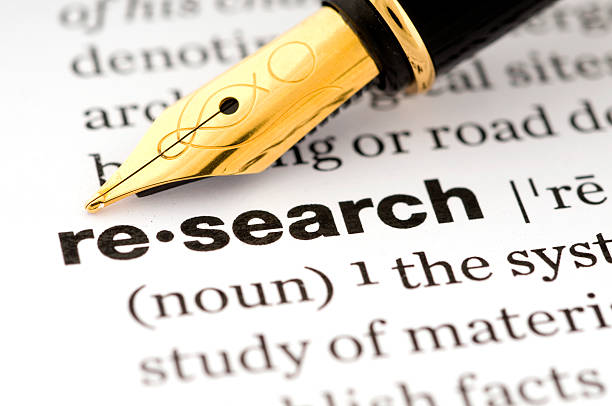 Research in a dictionary with a fountain pen stock photo