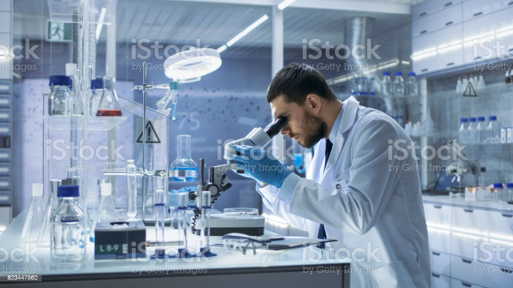 Research Scientist Looks into Microscope. He's Conducts Experiments in Modern Laboratory. royalty-free stock photo
