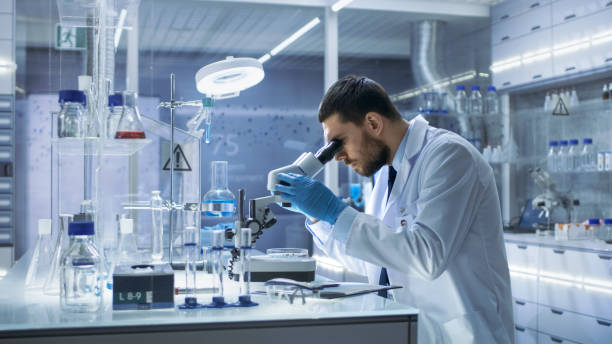 Research Scientist Looks into Microscope. He's Conducts Experiments in Modern Laboratory. stock photo