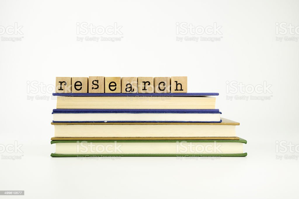 Research word on wood stamps and books stock photo