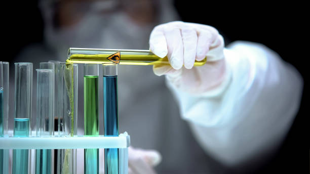 Researcher adding liquid from test tube with fire symbol, warning sign, danger stock photo