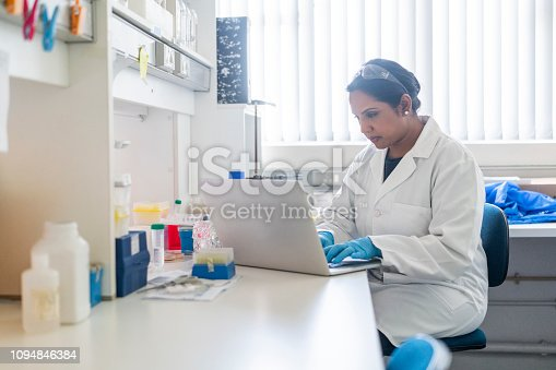 Mature scientist using laptop in laboratory. Confident female researcher is analyzing medical data. She is wearing lab coat.