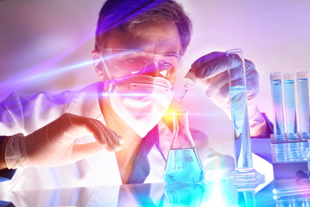 Researcher and chemical containers with lights behind the table stock photo