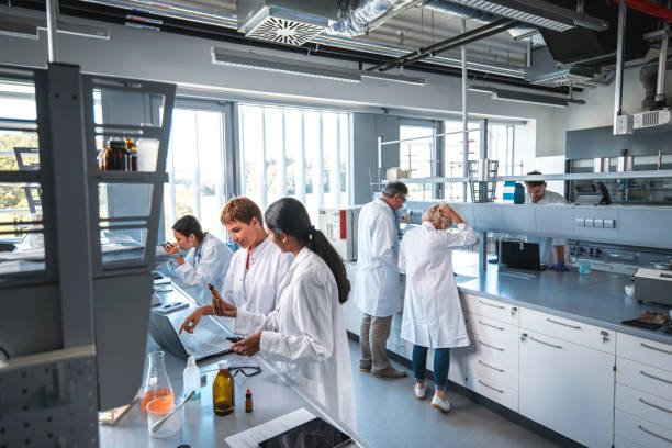 Researcher discussing with colleague in laboratory stock photo