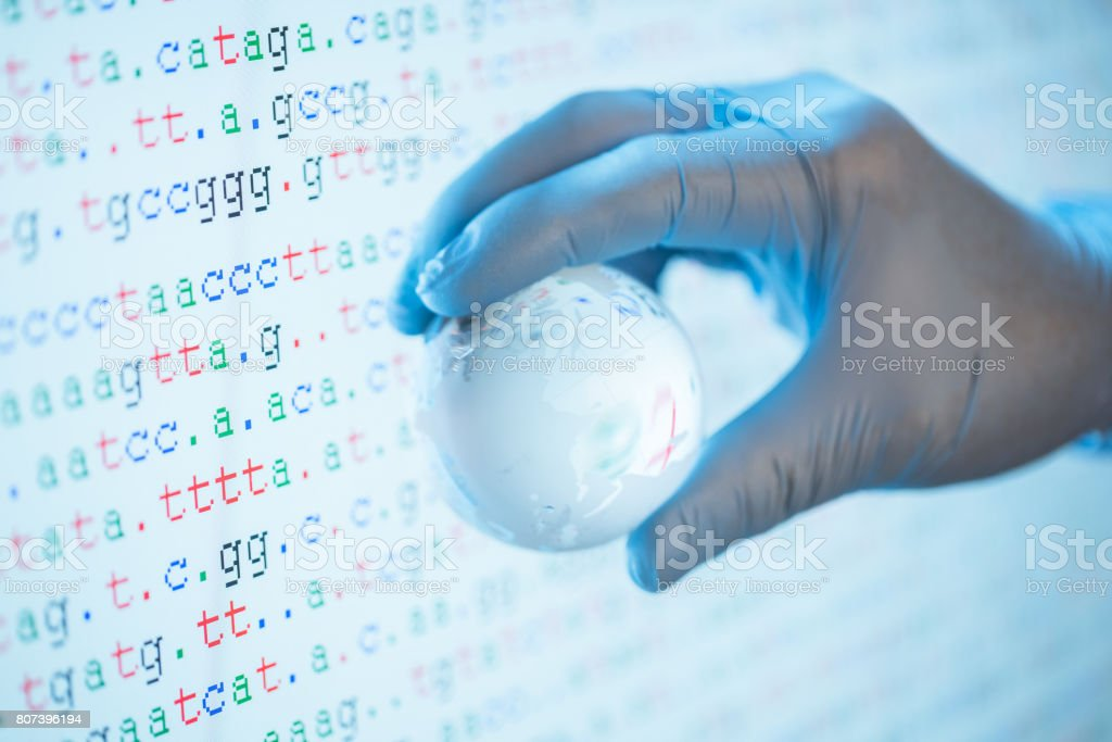 Researcher hand with blue glove hold one crystal global ball with DNA sequence as background stock photo