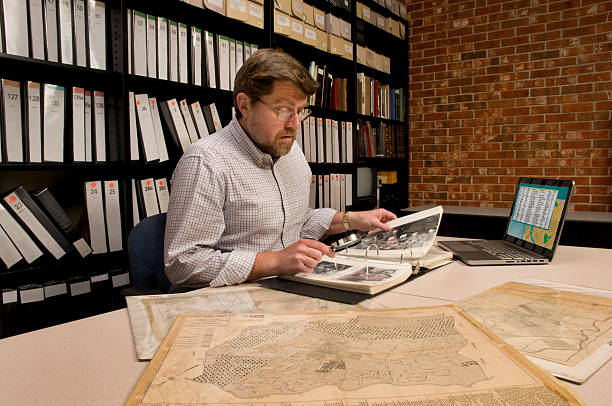 researcher in archive examining maps and other archival materials - curator stock pictures, royalty-free photos & images