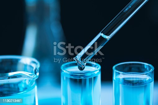 istock Researcher with glass laboratory chemical test tubes with liquid for analytical , medical, pharmaceutical and scientific research concept. 1130213461