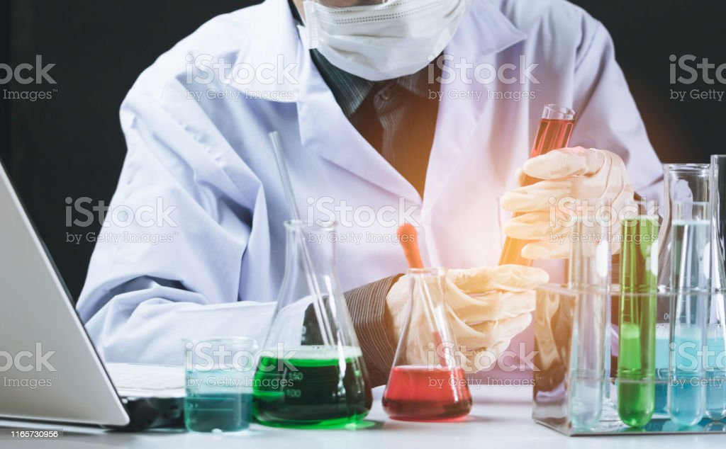 Researcher with glass laboratory chemical test tubes with liquid for...