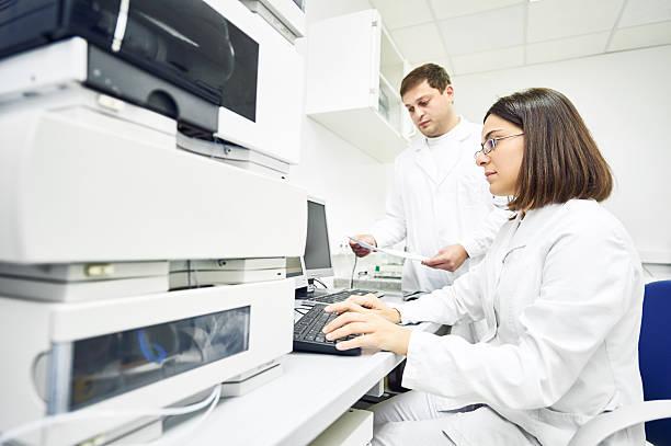 Researchers analyzing liquid chromatography data stock photo