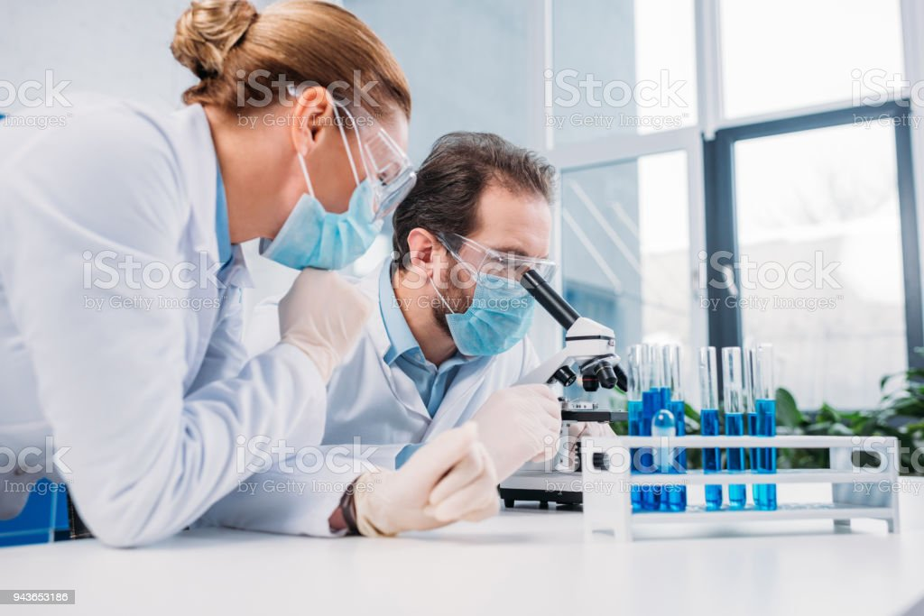 researchers in white coats and medical masks working with reagents together in lab stock photo